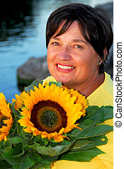 Woman sunflowers - Portrait of a mature woman with...
