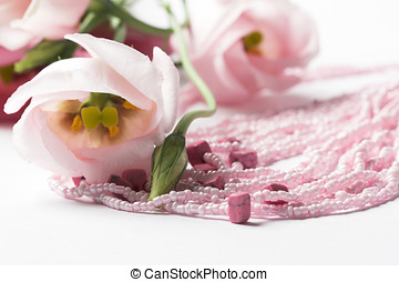 Pink necklace on white background with flower