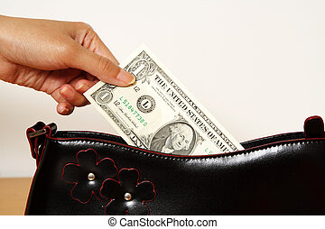 Shopping time - A woman taking out one dollar bill from a...