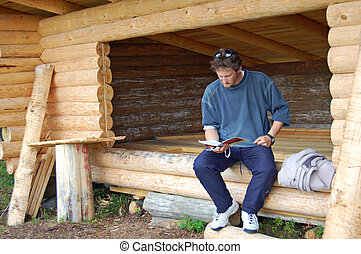 Log shelter - Man sitting in a new log lean-to shelter