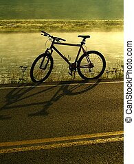 Lakeshore Biking - A bike rests on the side of a lake and a...