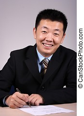 Businessman Writting - An asian businessman writting a...