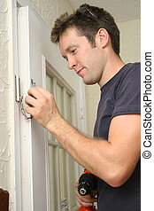 Home Improvement - Man installing door chain.