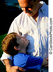 Father son happy - Son and father looking at each other and...