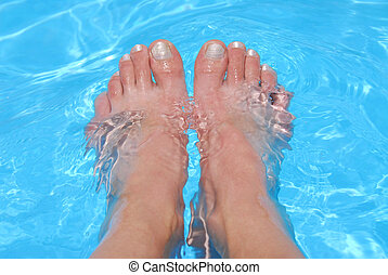 Feet in water - Woman\\\'s feet cooling in clear blue water