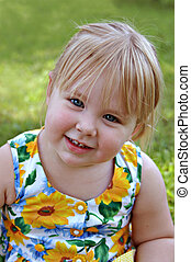 Female Toddler - Happy, healthy female toddler sitting...