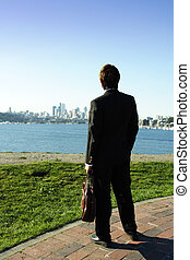 Businessman looking towards downtown buildings