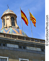 Spanish flags waving in the wind above the Palau de la...