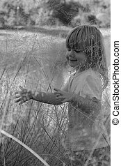 little girl playing in the weeds