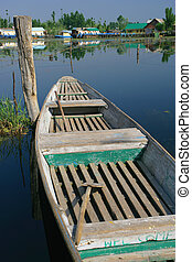 Welcome row boat - Old row boat tied to a post in Kashmir,...