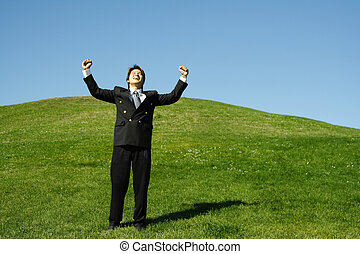 Happy businessman with arms up in the air