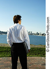 Businessman - A businessman carrying a laptop relaxing at a...