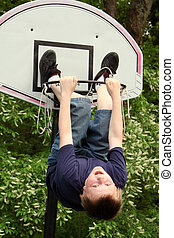 The Ball, Not You - Boy hanging from a basketball hoop, with...