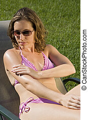 Sunscreen - Model Release 352 Woman in mid 20s applying...