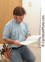 Electrician Reads the Manual - An electrician reading the...