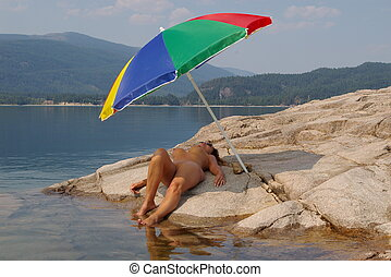 Beach Shade 7 - Nude female sun bather under a beach...