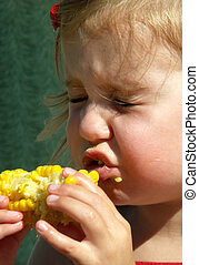 litle girl eating corn on the cob - little girl with eyes...