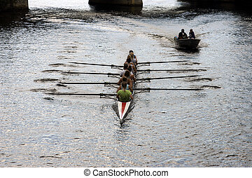 Crew team members row together on river
