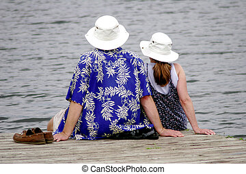Good company - Couple sitting together on dock overlooking...