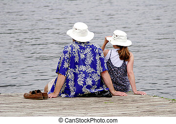 Sitting on the dock of the bay - Couple sitting together on...
