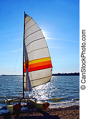 Sailboat backlit - Catamaran on a beach with backlit sail
