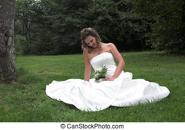 Beautiful bride sitting on a field