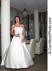 Beautiful bride standing with a single white rose in her...
