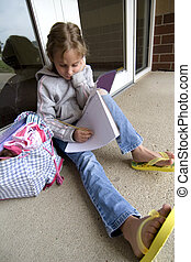 School assignment - Young grade school age girl does school...