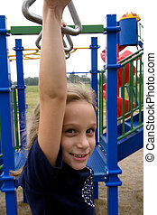 Hanging around - Young girl plays on school playground...