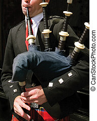 Bagpiper blowing his pipes in Edinburgh, Scotland.