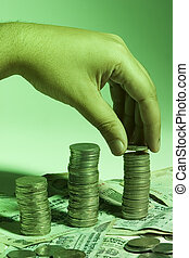Mans hand placing coin on stack of change