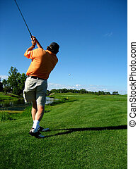 Golfer - A man watches his golf shot after he strikes the...