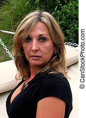 Blond with hammock - A blond woman is sitting on a hammock....