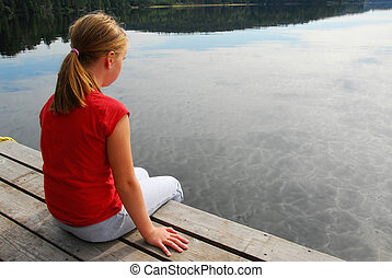 Girl child dock - Young girl dipping feet in the lake from...