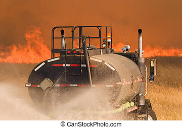 Fighting fire - A water truck helps to fight a large grass...