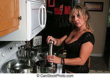 Woman cooking pepper - A blond woman is standing at a stove...