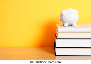 Saving for college - A piggy bank on top of a stack of...