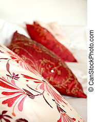 Red Pillows - Three pillows on a white couch with an Indian...