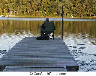 man on dock - man sitting on a dock at sunset, fishing in...