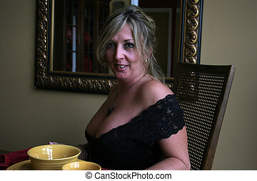At table and ready - A blond woman wearubg a black, low cut...