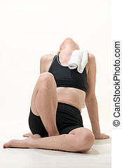 work out exhaustion - Attractive woman with towel sitting...
