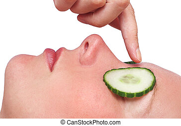 Cucumber Facial - Womans face with cucumber slices and...