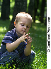 Walk in park - The child sits in a grass