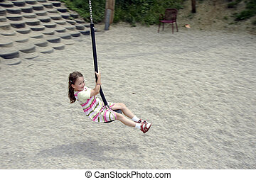 young girl swinging 01 - young girl swinging on a playground