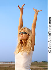 beach babe - lovely blond raising hands to the sun