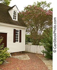 Quaint Home - A small cottage with an brick walkway and...