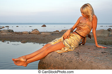 day at the seashore - lovely girl relaxing on the rock