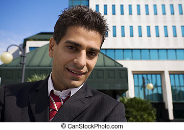 business center - young businessman in front of a building