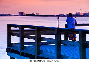 Fishing in Florida - Man fishing off a pier in Florida at...