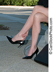 Sore feet - legs of businesswoman in high heels sitting and...